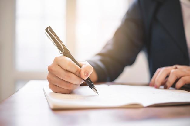 Ciérrese para arriba de la escritura femenina de la mano en el libro.