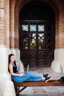 Ciérrese para arriba de un estudiante universitario de sexo femenino que se sienta en un césped usando su computadora portátil en un día soleado.
