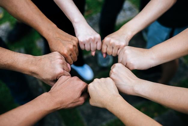 Ciérrese para arriba de los estudiantes que colocan las manos que hacen gesto del topetón del puño.