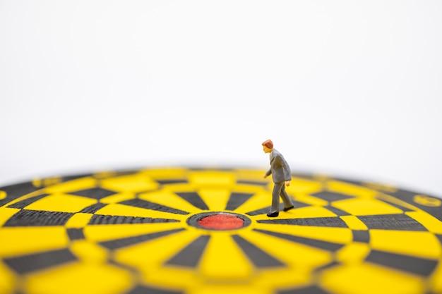 Ciérrese para arriba de la figura miniatura del hombre de negocios que camina al centro del tablero de dardo con blanco.