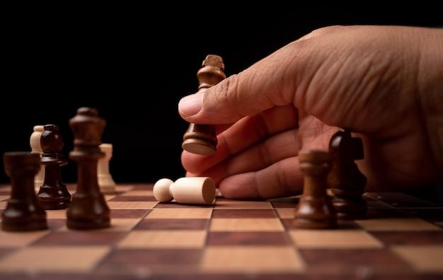 Ciérrese para arriba de la figura móvil del ajedrez del hombre de negocios confiado de las manos en juego del éxito de la competencia.