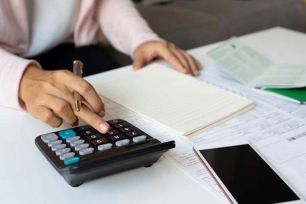 Ciérrese para arriba del gasto mensual de calculating de la empresaria en su escritorio. concepto de ahorro de vivienda. concepto de pago financiero y a plazos.