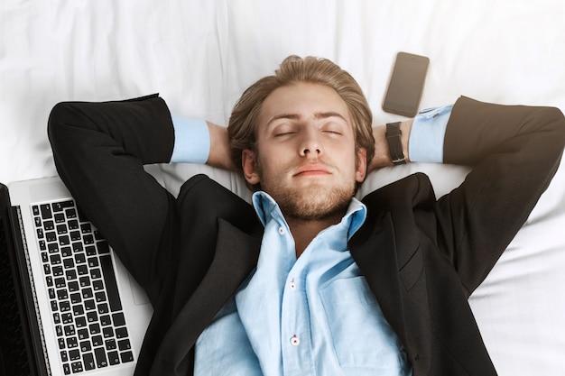 Ciérrese para arriba del gerente joven hermoso en traje elegante que miente en cama con las manos debajo de la cabeza, duerma con la computadora portátil y el teléfono inteligente después del trabajo duro.