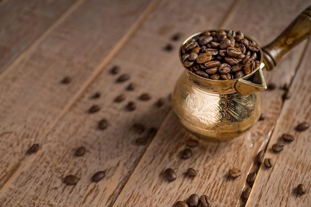 Ciérrese para arriba de los granos de café asados frescos en cezve en la tabla de madera.