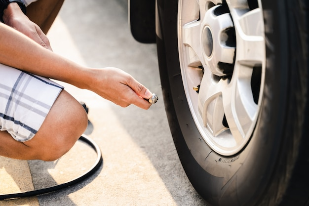 Ciérrese para arriba del hombre asiático que infla el neumático en la gasolinera.