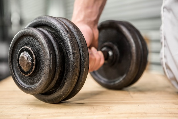 Ciérrese para arriba del hombre que lleva a cabo pesa de gimnasia en el gimnasio del crossfit