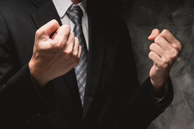 Ciérrese para arriba de hombre en traje negro con gesto de mano en fondo gris del grunge.