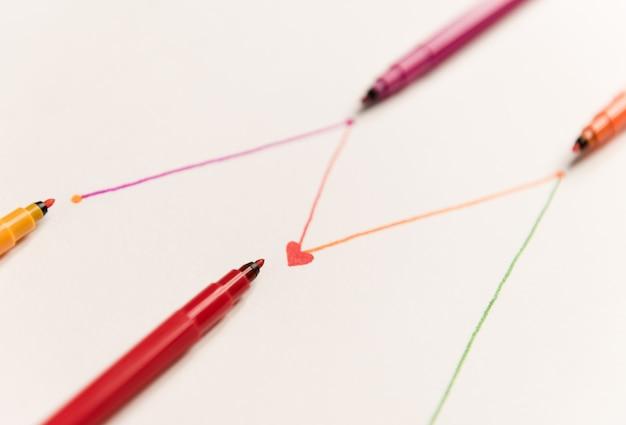 Ciérrese para arriba de las líneas conectadas pintadas con los marcadores rojos coloridos en el papel blanco. líneas para gráficos, horario