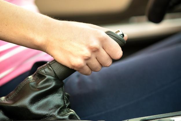 Ciérrese para arriba de la mano femenina del conductor que sostiene el freno de mano en un coche.
