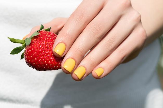 Ciérrese para arriba de la mano femenina con la manicura bastante amarilla del diseño del clavo que sostiene la fresa madura.