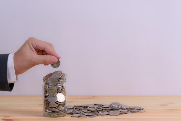 Ciérrese para arriba de la mano del hombre de negocios que pone las monedas en la tabla en su oficina en finanzas
