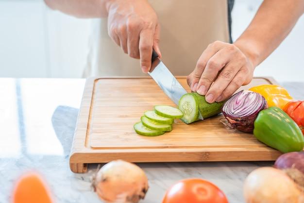 Ciérrese para arriba de la mano del hombre que cocina y que corta el vehículo en la cocina para preparar la cena