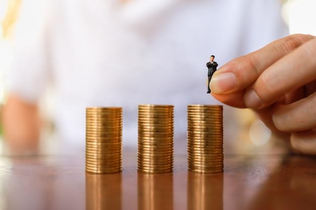 Ciérrese para arriba de la mano del hombre que sostiene a la figura miniatura del hombre de negocios gente y que pone al top de la pila de monedas de oro.