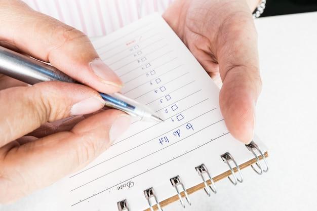 Ciérrese para arriba de la mano del hombre que sostiene y que escribe el cuaderno con la escritura para hacer la lista.