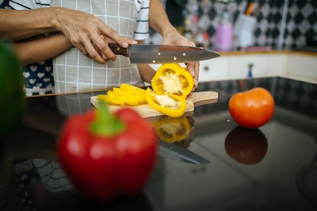 Ciérrese para arriba de la mano de la mamá que enseña a su hija que prepara y que taja la verdura.