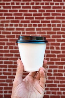 Ciérrese para arriba de la mano masculina que sostiene la taza de café del libro blanco, contra una pared de ladrillo roja. disfrutando de un café para llevar