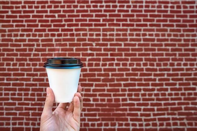 Ciérrese para arriba de la mano masculina que sostiene la taza de café del libro blanco, contra una pared de ladrillo roja.