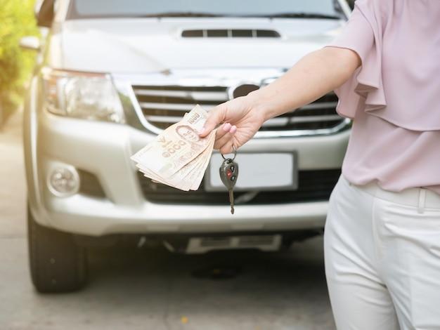Ciérrese para arriba de la mano que lleva a cabo la llave del dinero y del coche contra un coche. seguros, préstamos y finanzas