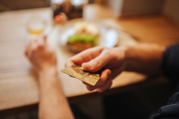 Ciérrese para arriba de la mano del ser humano que sostiene una tarjeta plástica. se lo está mostrando a la cámara. guy va a pagar la cena.