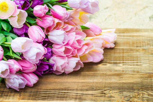 Ciérrese para arriba de manojo de tulipanes coloridos en fondo de madera