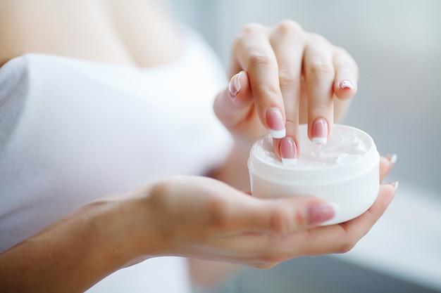 Ciérrese para arriba de las manos femeninas que sostienen el tubo de la crema, manos hermosas de la mujer con las uñas de manicura naturales que aplican la crema cosmética de manos en la piel suave sedosa sana.