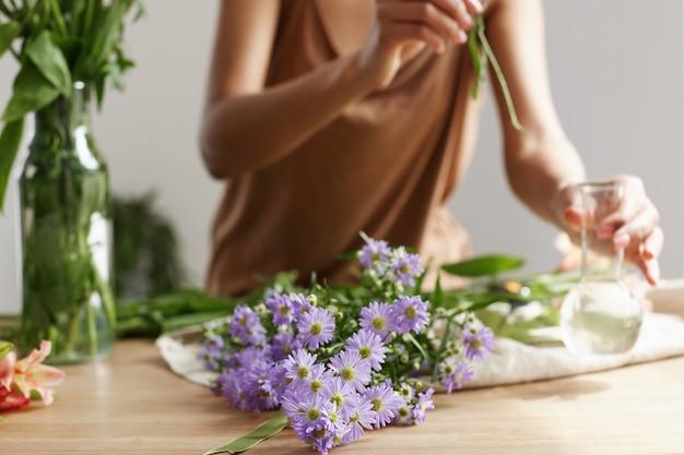 Ciérrese para arriba de las manos del florista que hacen el ramo de flores en el lugar de trabajo.
