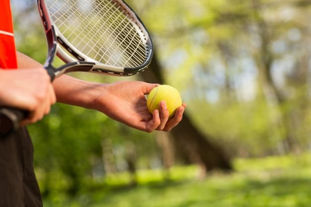 Ciérrese para arriba de las manos de los hombres sostienen una raqueta y una bola de tenis en el fondo verde.