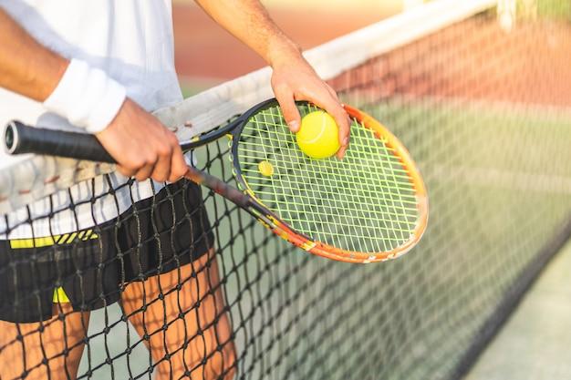 Ciérrese para arriba de las manos del jugador de tenis que sostienen la estafa con la bola.