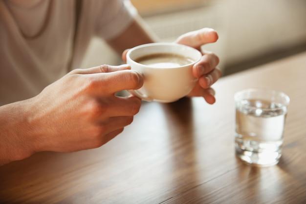 Ciérrese para arriba de las manos masculinas que sostienen la taza de café, la educación y el concepto del negocio