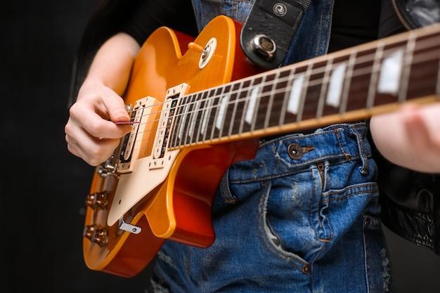 Ciérrese para arriba de las manos de la muchacha en la guitarra sobre fondo negro.