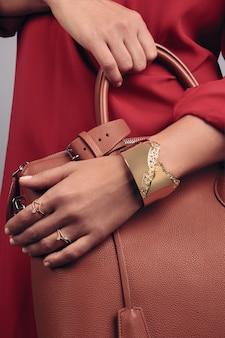 Ciérrese para arriba en las manos de la muchacha que sostienen el bolso de mano de cuero marrón