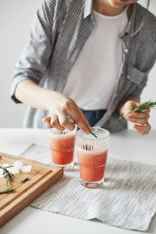 Ciérrese para arriba de las manos de la mujer que decoran el smoothie sano de la desintoxicación del pomelo con romero.