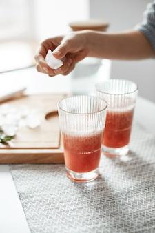 Ciérrese para arriba de las manos de la mujer que ponen pedazos del hielo en vidrios con el smoothie sano de la desintoxicación de la toronja.