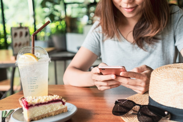 Ciérrese para arriba de las manos de las mujeres que sostienen el teléfono móvil en café.