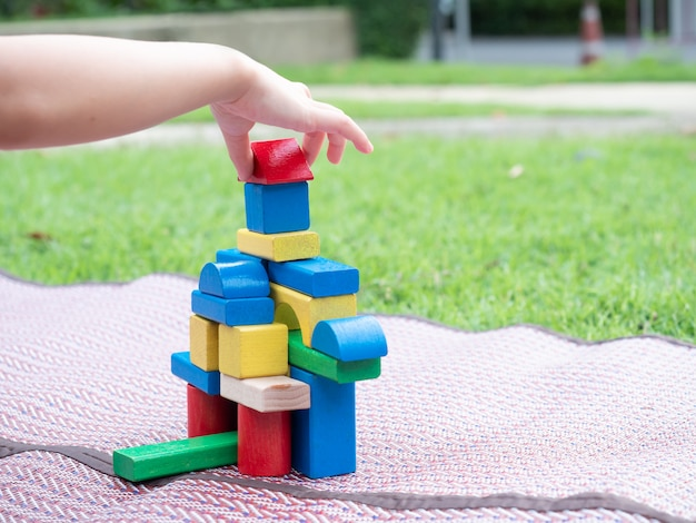 Ciérrese para arriba en las manos de un niño pequeño que juega bloques de madera en la estera en el jardín.