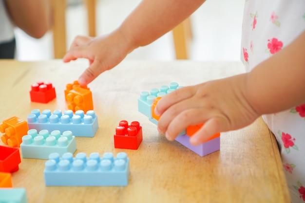 Ciérrese para arriba de las manos del niño que juegan con los juguetes coloridos del conector en la tabla. juguetes educativos para niños de preescolar y jardín de infantes.
