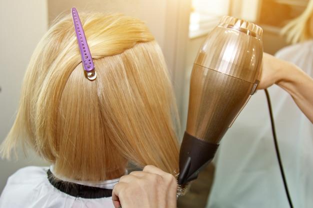 Ciérrese para arriba de las manos del peluquero que secan el cabello humano con el equipo. mujer sosteniendo un peine. de cerca. foto macro.