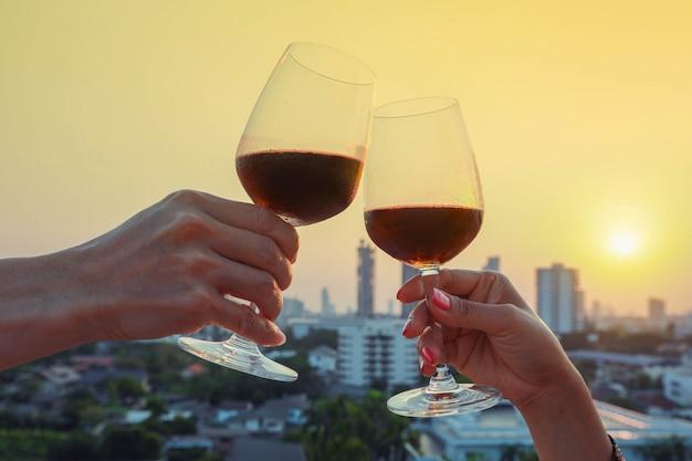 Ciérrese para arriba en las manos que sostienen la copa de vino rojo en balcón durante la puesta del sol, concepto de la celebración