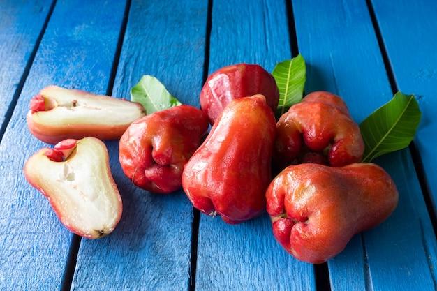 Ciérrese para arriba de manzanas color de rosa en la tabla de madera azul