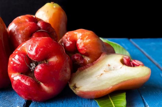 Ciérrese para arriba de las manzanas de rose en la tabla de madera azul con el fondo negro