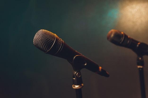 Ciérrese para arriba del micrófono en etapa en fondo de la falta de definición de la sala de audiencia.