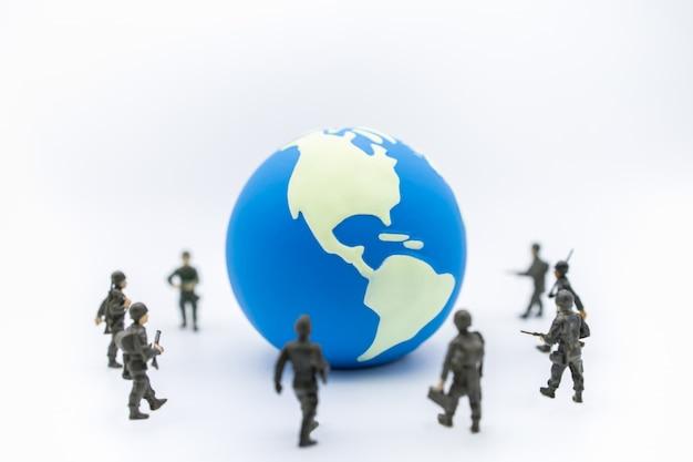 Ciérrese para arriba de mini bola del mundo con el grupo de figura miniatura del soldado que se coloca alrededor.