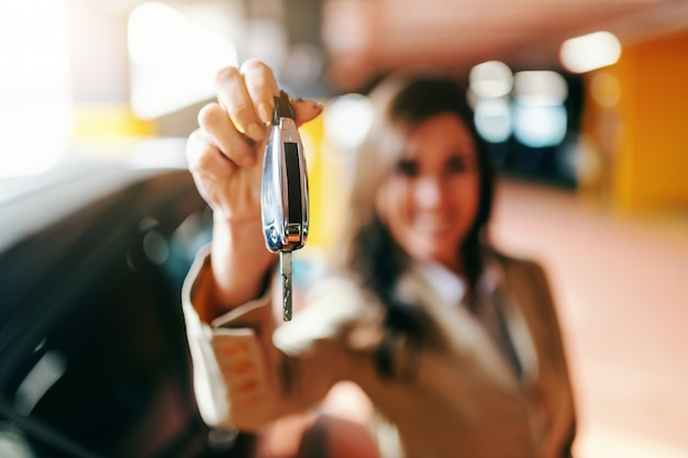 Ciérrese para arriba de la morenita hermosa sonriente que lleva a cabo llaves del coche en el estacionamiento. enfoque selectivo en mano con llaves.