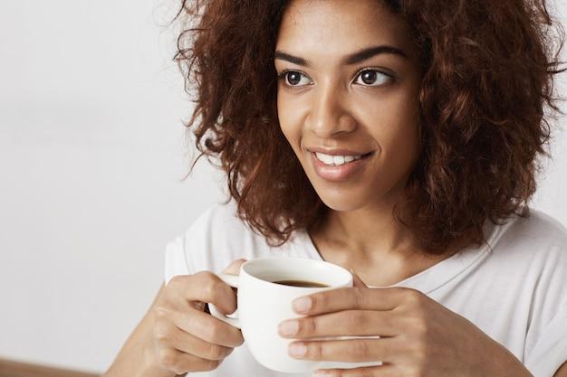 Ciérrese para arriba de la muchacha africana hermosa que sonríe sosteniendo la taza de café.