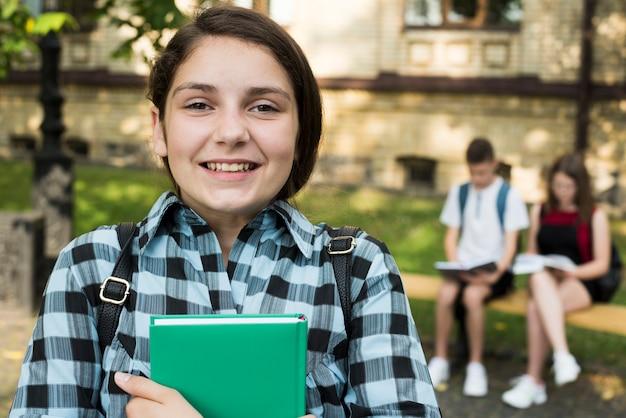Ciérrese para arriba de la muchacha sonriente del highschool que sostiene el libro en manos