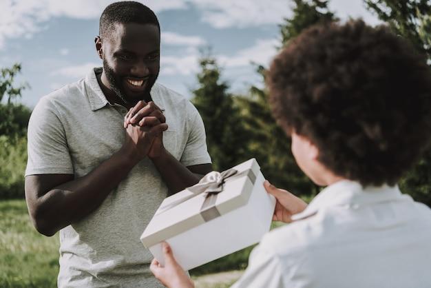 Ciérrese para arriba del muchacho da el regalo al padre negro feliz.