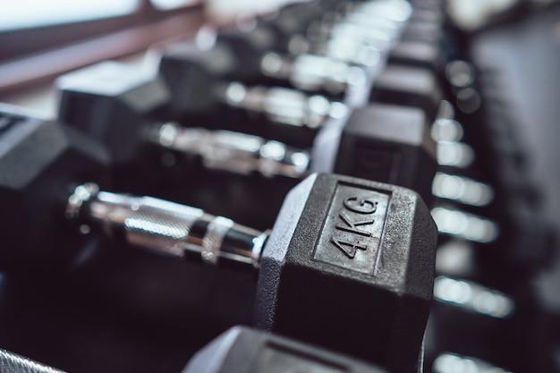 Ciérrese para arriba de muchas pesas de gimnasia del metal en el estante en gimnasio de deporte.