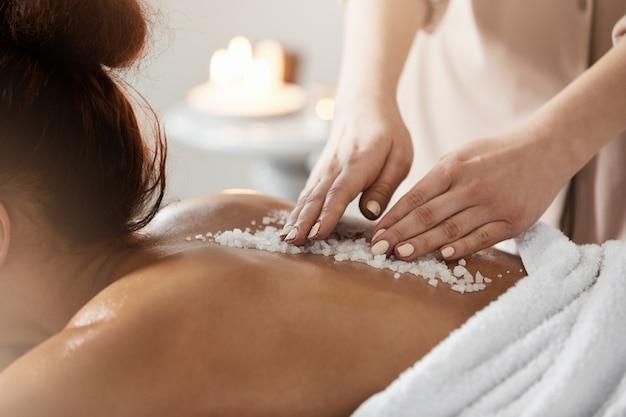 Ciérrese para arriba de la mujer africana que se relaja disfrutando de masaje de la salud del balneario con la sal del mar.