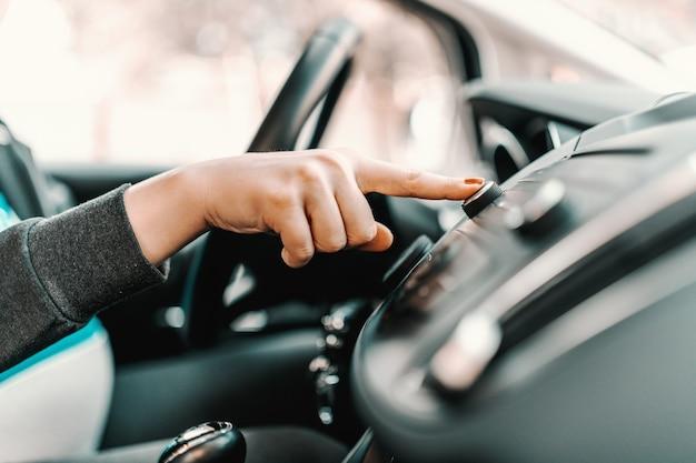 Ciérrese para arriba de la mujer caucásica embarazada joven que conduce el coche y que cambia la estación de radio.