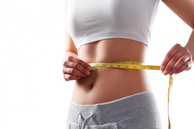 Ciérrese para arriba de la mujer delgada que mide el tamaño de su cintura con cinta métrica.